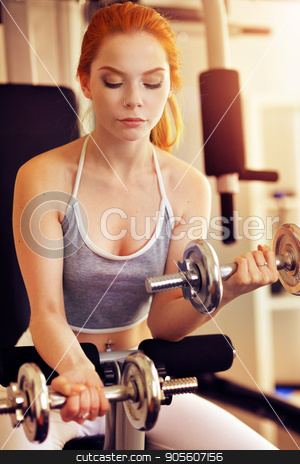 Young woman training in gym stock photo, Portrait of a sporty young woman training in gym by Ruslan Huzau