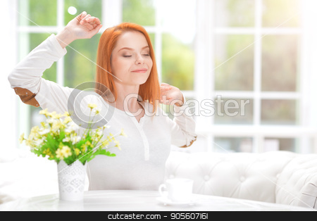 young woman stretching oneself stock photo, Beautiful young woman stretching oneself while sitting at table by Ruslan Huzau