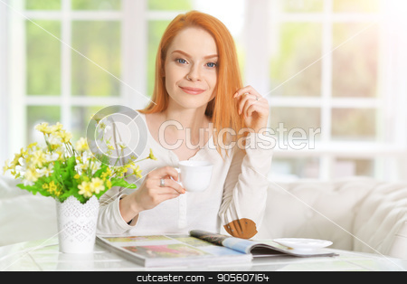young woman with cup of coffee stock photo, beautiful young woman with cup of coffee and magazine by Ruslan Huzau