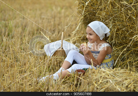Little girl having lunch stock photo, Little girl having lunch while sitting near stack of hay by Ruslan Huzau