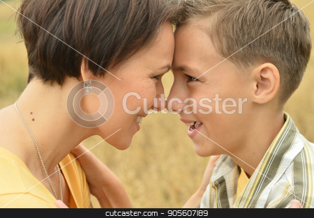 Mother and son standing face to face stock photo, Mother and son standing face to face outdoors by Ruslan Huzau