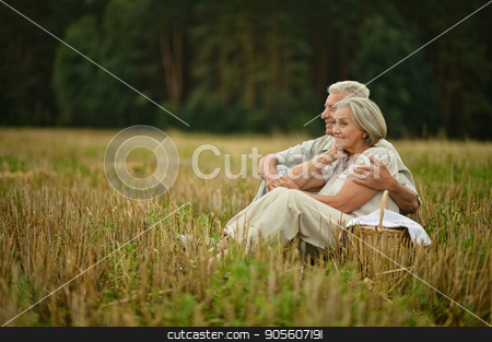Senior couple on mowed field of wheat  stock photo, Happy senior couple on mowed field of wheat by Ruslan Huzau