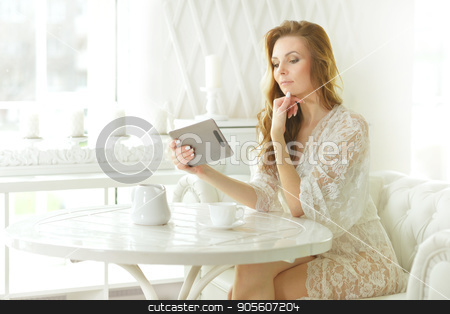 Beautiful woman with tablet in hands stock photo, Beautiful young woman with tablet in hands by Ruslan Huzau
