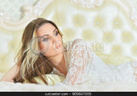 Attractive young woman  stock photo, Attractive young woman lying on vintage bed by Ruslan Huzau