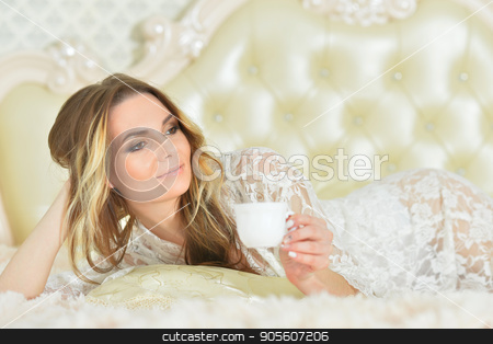 Beautiful young woman  white cup of coffee stock photo, Beautiful young woman lying on bed and holding white cup of coffee by Ruslan Huzau