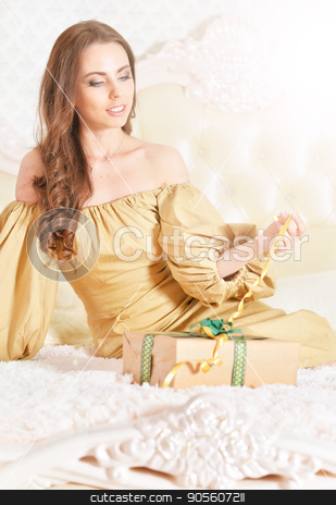 Beautiful young woman with gift box stock photo, Beautiful young woman in golden dress with gift box by Ruslan Huzau