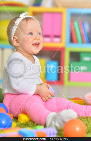 Little child playing with colorful toys  stock photo, Adorable little child playing with colorful toys in childrens room by Ruslan Huzau