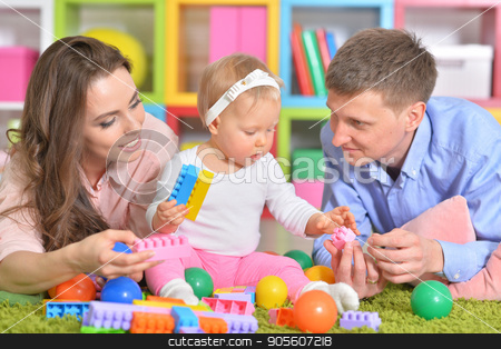 Happy parents playing with little daughter stock photo, Happy parents playing with adorable little daughter by Ruslan Huzau