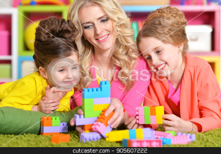 young woman playing with daughters stock photo, Beautiful young woman playing with her daughters by Ruslan Huzau