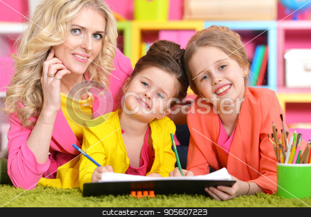 Mother with daughters drawing  stock photo, Mother with her daughters drawing in room with bookshelves by Ruslan Huzau