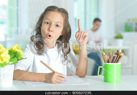 little girl drawing with pencil stock photo, Cute little girl sitting at table and drawing with pencil by Ruslan Huzau