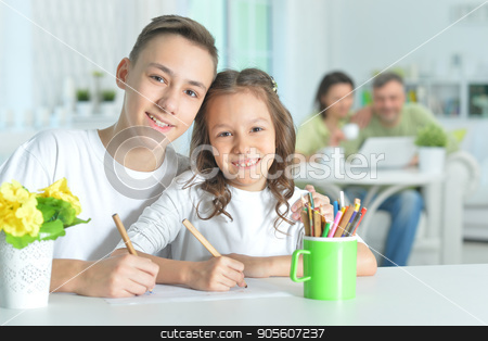 Brother and sister spending time together stock photo, Brother and sister sitting at table and spending time together by Ruslan Huzau