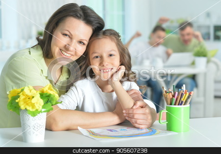 Mother and daughter sitting at table stock photo, Mother and daughter sitting at table, mother hugging her daughter by Ruslan Huzau