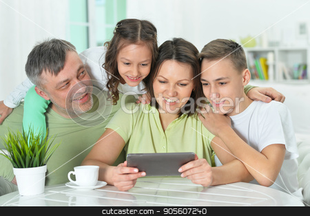 family sitting at table with tablet stock photo, Happy family sitting at table with tablet by Ruslan Huzau