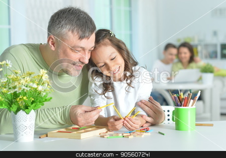 Father and daughter playing together stock photo, Father and daughter sitting at table and playing together by Ruslan Huzau