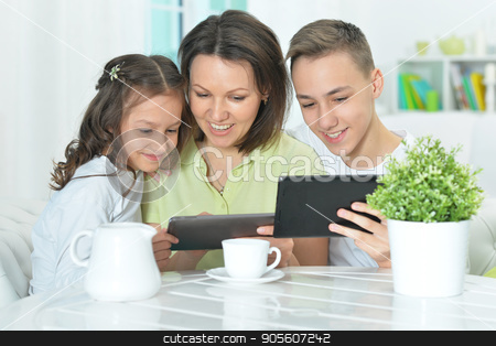 family using tablets stock photo, Happy family sitting at table and using digital tablets by Ruslan Huzau