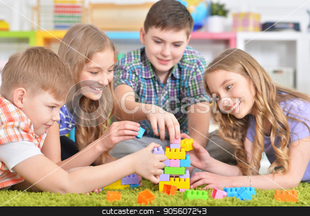 Group of children playing together stock photo, Group of children playing together while lying on floor with green carpet by Ruslan Huzau