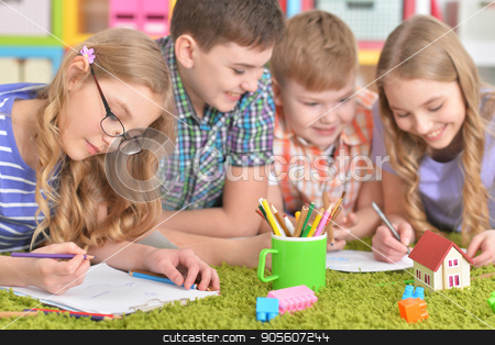 Group of children drawing with pencils stock photo, Group of children lying on floor with green carpet and drawing with pencils by Ruslan Huzau