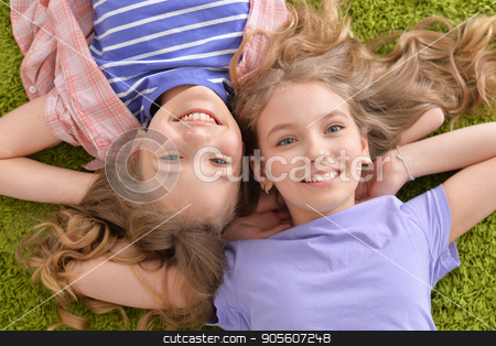 Two pretty little girls  stock photo, Two pretty little girls lying on green carpet and looking at camera by Ruslan Huzau