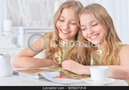 Cute twin sisters with modern magazine stock photo, Cute twin sisters sitting at kitchen table with modern magazine by Ruslan Huzau