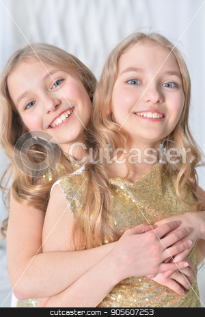 Portrait of a cute twin sisters stock photo, Portrait of a cute twin sisters embrace by Ruslan Huzau