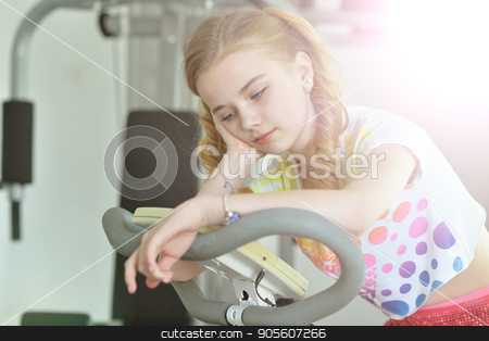 Tired little girl sitting on treadmill stock photo, Tired little girl sitting on treadmill with hand on her cheek by Ruslan Huzau