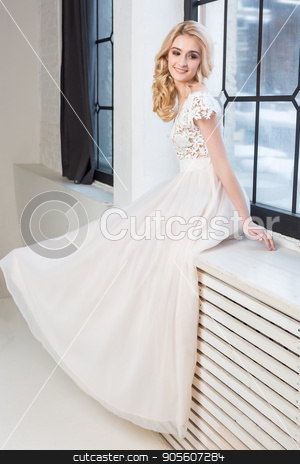fashionable wedding gown, beautiful blonde model, bride hairstyle and makeup concept - graceful young woman in white dress sitting on the windowsill indoors, smiling female posing in the studio. stock photo, fashionable wedding gown, beautiful blonde model, bride hairstyle and makeup concept - graceful young woman in white dress sitting on the windowsill indoors, smiling female posing in the studio by Dmitry