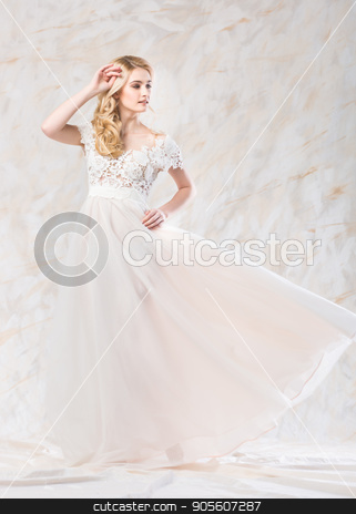 fashionable wedding dress, beautiful blonde, bride hairstyle and makeup concept - posing young pretty woman in long luxury white gown indoors on light background, romantic female model in a studio. stock photo, fashionable wedding dress, beautiful blonde, bride hairstyle and makeup concept - posing young pretty woman in long luxury white gown indoors on light background, romantic female model in a studio by Dmitry