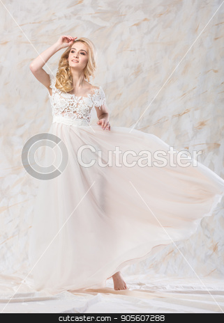 fashionable wedding dress, beautiful blonde, bride hairstyle and makeup concept - posing young woman in long luxury white gown indoors on light background, smiling female model in a studio. stock photo, fashionable wedding dress, beautiful blonde, bride hairstyle and makeup concept - posing young woman in long luxury white gown indoors on light background, smiling female model in a studio by Dmitry