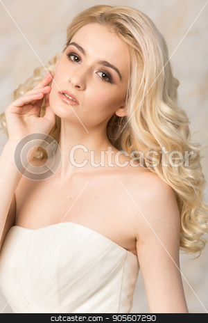 fashionable gown, beautiful blonde model, bride hairstyle and makeup concept - portrait of young romantic lady in white festive wedding dress, slender pretty woman stand indoors on light background. stock photo, fashionable gown, beautiful blonde model, bride hairstyle and makeup concept - portrait of young romantic lady in white festive wedding dress, slender pretty woman stand indoors on light background by Dmitry