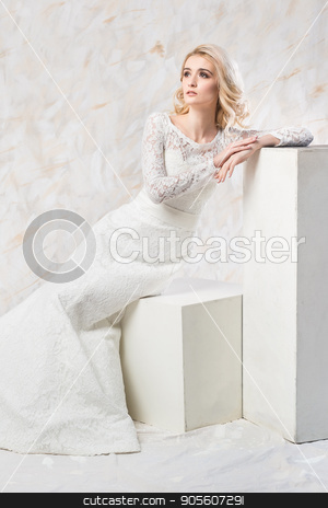 fashionable wedding dress, beautiful blonde model, bride hairstyle and makeup concept - splendid young woman in luxury white gown sitting indoors on light background, female posing in the studio. stock photo, fashionable wedding dress, beautiful blonde model, bride hairstyle and makeup concept - splendid young woman in luxury white gown sitting indoors on light background, female posing in the studio by Dmitry