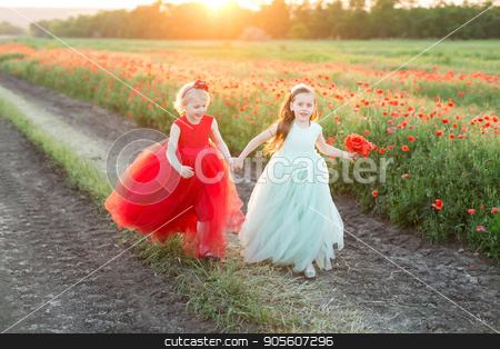freedom, frendship, country, happiness concept - in gold light of sun two lovely girls in beautiful feast dresses in bright red and light blue shadows running in rural road near the field of poppies stock photo, freedom, frendship, country, happiness concept - in gold light of sun two lovely girls in beautiful feast dresses in bright red and light blue shadows running in rural road near the field of poppies by Dmitry