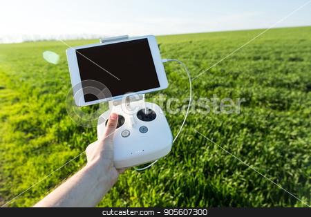 quadcopter flights outdoors, aerial imagery and tech hobby, recreation concept - operator holds white drone remote control with installed tablet PC for flight view, field of green grass on background. stock photo, quadcopter flights outdoors, aerial imagery and tech hobby, recreation concept - operator holds white drone remote control with installed tablet PC for flight view, field of green grass on background by Dmitry