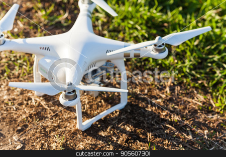 quadcopter summer outdoors, aerial imagery and hobby, recreation concept - quadrocopter landed on earth with grass, white superb drone fuselage with four propellers and high quality digital camera. stock photo, quadcopter summer outdoors, aerial imagery and hobby, recreation concept - quadrocopter landed on earth with grass, white superb drone fuselage with four propellers and high quality digital camera by Dmitry