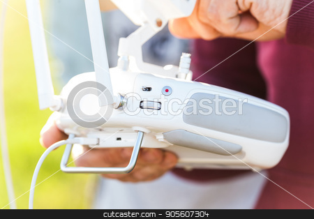 quadcopter flight outdoors, aerial imagery and tech hobby, recreation concept - closeup on white remote radio control in pilot hands, modern high-tech solution for video filming and joy flying. stock photo, quadcopter flight outdoors, aerial imagery and tech hobby, recreation concept - closeup on white remote radio control in pilot hands, modern high-tech solution for video filming and joy flying by Dmitry