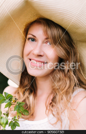 spring, summer, holidays, nature, beauty, decoration, gardening concept - close-up of beautiful blue-eyed woman in straw hat with flowing hair and friendly smile holding few twigs stock photo, spring, summer, holidays, nature, beauty, decoration, gardening concept - close-up of beautiful blue-eyed woman in straw hat with flowing hair and friendly smile holding few twigs by Dmitry