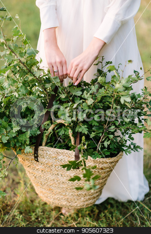 nature, ecology, environment, beauty, holidays, countrylife, lifestyle concept - woman in white feast dress holding straw handbag with fresh green oak branches stock photo, nature, ecology, environment, beauty, holidays, countrylife, lifestyle concept - woman in white feast dress holding straw handbag with fresh green oak branches by Dmitry