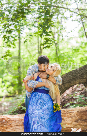 Boy kissing his girlfriend on the cheek stock photo, Boy kissing his girlfriend on the cheek outdoors by Satura86