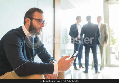 Businessman using smart phone while sitting in waiting room. stock photo, Businessman using smart phone while sitting and waiting in office building lobby. Business people talking in background. by kasto