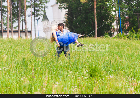 Young man carrying his girlfriend in his arms on grass field. Couple having fun in nature on a summer day stock photo, Shot of young man carrying his girlfriend in his arms on grass field. Couple having fun in nature on a summer day by Satura86