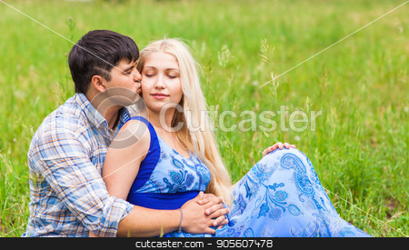 Happy young couple relaxing on the lawn in a summer park. Love concept. Vacation stock photo, Happy young couple relaxing on the lawn in a summer park. Love concept. Vacation by Satura86