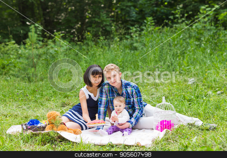 Family on picnic at sunny day stock photo, Family on picnic at sunny day. Happy Mixed Race Family Having a Picnic and Playing In The Park by Satura86