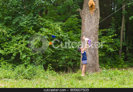 happy family. Mother throws up baby, playing outdoors stock photo, happy family - Mother throws up baby, playing outdoors by Satura86