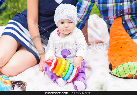 baby and mother and father playing on the green grass, family picnic close-up stock photo, baby and mother and father playing on the green grass, family picnic by Satura86