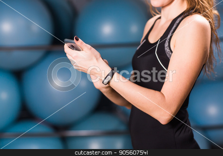 Close-up of female hands with fitness tracker and smartphone in gym stock photo, Young woman with fitness tracker and smartphone in gym by Satura86