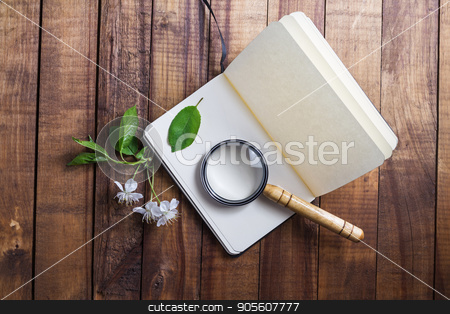 Notebook and magnifier stock photo, Photo of blank opened notebook, magnifier, cherry flowers and green leaves on vintage wooden table background. Stationery elements. Template for placing your design. Responsive design mockup. by Veresovich
