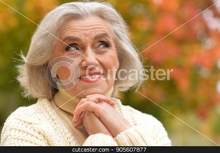 senior woman resting in  park stock photo, Happy senior woman resting in autumnal park by Ruslan Huzau