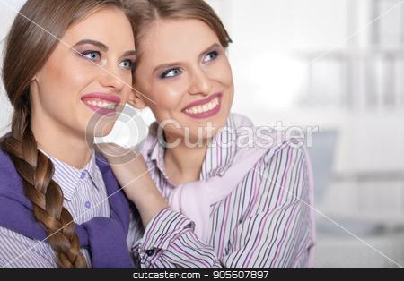 Two young beautiful girls stock photo, Two young smiling beautiful girls in office by Ruslan Huzau