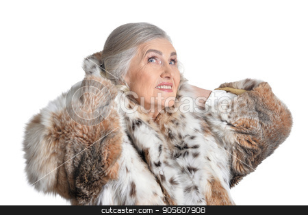 Senior woman in fur  stock photo, Senior woman in fur smiling with hands behind head on white background by Ruslan Huzau
