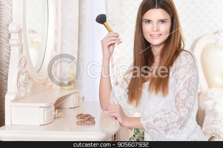 Young woman sitting at dressing table stock photo, Beautiful young woman sitting at dressing table with brush by Ruslan Huzau